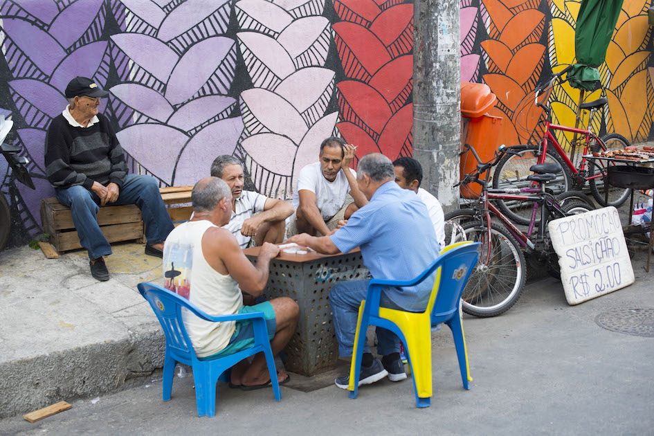 Men playing dominoes on the streets of the Santa Marta Favela, Rio de Janerio.
