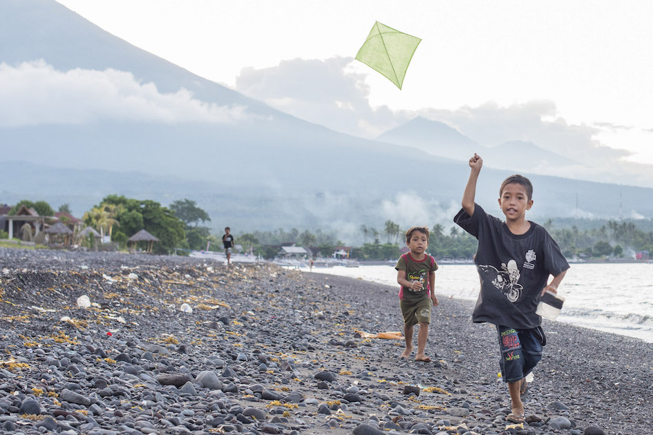 Kids flying their kites on the black sands of Amed, Bali