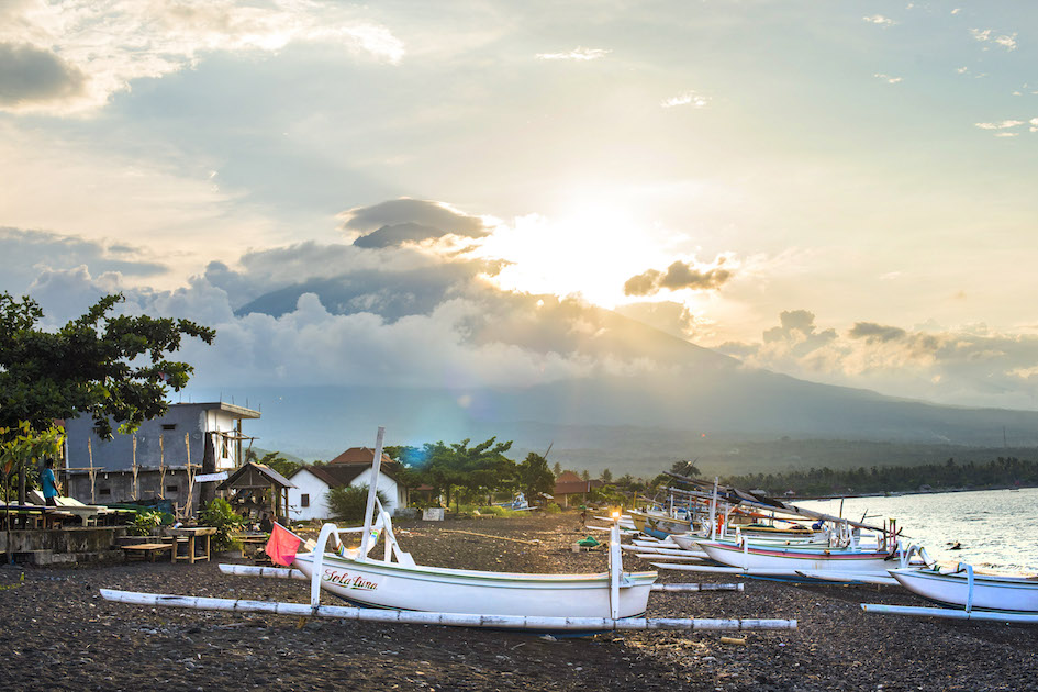 The last rays of sun on the sleepy beach of Amed before it sets behind Mt. Agung, Bali