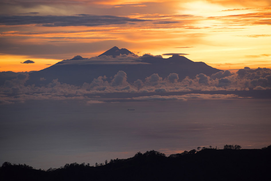 The sunrise over Lombok's volcano Mt. Rinjani seen from the top of Bali's volcano Mt. Batur
