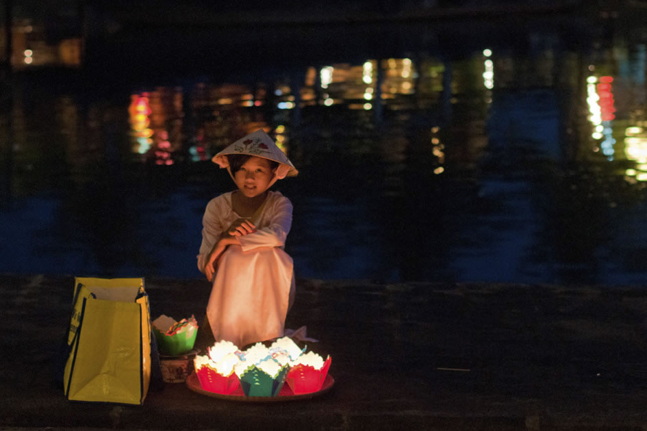 Lantern sales girl sitting along the Thu Bon River, Hoi An